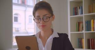 Tiro do close up da mulher de negócios caucasiano bonita nova nos vidros que consulta na tabuleta no escritório dentro vídeos de arquivo