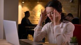 Tiro do close up da mulher de negócios caucasiano bonita nova que tem uma dor de cabeça ao datilografar no portátil dentro no imagens de stock royalty free