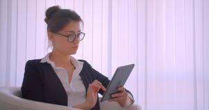 Tiro do close up da mulher de negócios caucasiano bonita nova que trabalha na tabuleta que senta-se na poltrona que olha a câmera vídeos de arquivo