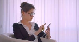 Tiro do close up da mulher de negócios caucasiano bonita nova que usa a tabuleta e mostrando a tela verde do croma ao assento da  video estoque