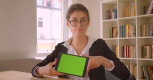 Tiro do close up da mulher de negócios caucasiano nova nos vidros usando a tabuleta e mostrando a croma verde a tela chave à câme video estoque