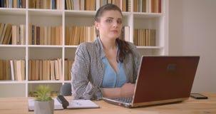 Tiro do close up da mulher de negócios caucasiano nova que usa o portátil que olha a câmera que sorri seguramente na biblioteca vídeos de arquivo