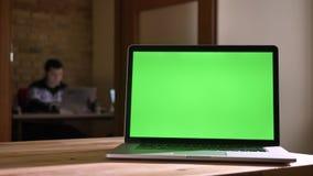 Tiro do close up da tela verde do portátil que coloca na mesa no escritório que indica dentro uma propaganda vídeos de arquivo