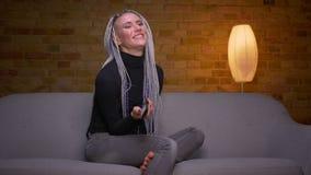 Tiro do close up da tevê de observação fêmea do moderno caucasiano atrativo novo e de usar o assento de controle remoto no sofá video estoque