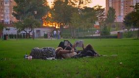 Tiro do close up das estudantes universitário que descansam e que colocam na grama no parque quando livros de leitura e sonhar ac filme
