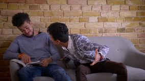 Tiro do close up de dois amigos masculinos novos que sentam-se no sof? junto dentro em um apartamento acolhedor Homem que olha ac video estoque