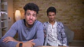 Tiro do close up de dois amigos novos e dos bloggers masculinos afro-americanos e indianos que fluem a fala viva na câmera filme