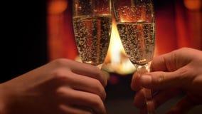 Tiro do close up de dois vidros do tinido das mãos completos do champanhe que comemora uma data da noite com a chaminé morna ac video estoque