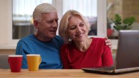Tiro do close up de pares felizes superiores usando o portátil na mesa com os copos com chá dentro em um apartamento acolhedor filme