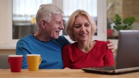 Tiro do close up de pares felizes superiores usando o portátil na mesa com os copos com chá dentro em um apartamento acolhedor na vídeos de arquivo