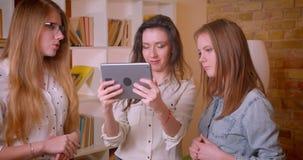 Tiro do close up de pares lésbicas bonitos novos falando ao corretor de imóveis fêmea sobre comprar uma utilização do apartamento