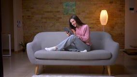 Tiro do close up de texting fêmea caucasiano moreno bonito novo na tabuleta e do sorriso felizmente sentando-se no sofá vídeos de arquivo