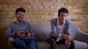 Tiro do close up dos amigos masculinos afro-americanos e indianos que jogam os jogos de vídeo que sentam-se junto no sofá dentro  video estoque