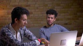 Tiro do close up dos estudantes masculinos indianos e afro-americanos que usam os portáteis que têm uma discussão dentro na bibli video estoque