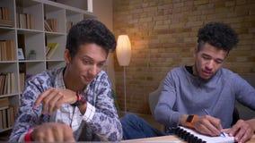 Tiro do close up dos estudantes masculinos indianos e afro-americanos que usam os portáteis que têm uma discussão e que tomam not filme