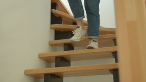 Tiro do close up dos pés fêmeas bonitos novos nas calças de brim e nas sapatilhas que andam em baixo em um apartamento acolhedor
