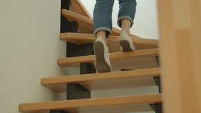 Tiro do close up dos pés fêmeas bonitos novos que andam em cima em um apartamento acolhedor