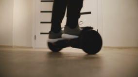 Tiro do close-up dos pés masculinos nas sapatilhas que movem-se ao redor na placa elétrica do pairo no escritório claro moderno c filme
