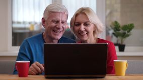 Tiro do close up dos pares felizes envelhecidos que mandam um vídeo chamar o portátil com os copos com chá na mesa e que acenam o vídeos de arquivo