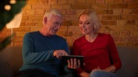 Tiro do close up dos pares felizes superiores que surfam meios sociais na tabuleta que senta-se no sofá dentro em um apartamento  video estoque