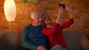 Tiro do close up dos pares felizes superiores que tomam selfies no telefone que senta-se no sofá dentro em um apartamento acolhed video estoque