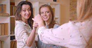 Tiro do close up dos pares lésbicas bonitos novos que compram um plano e que obtêm chaves de um corretor de imóveis que abraça al