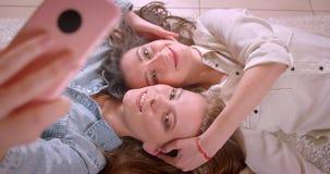 Tiro do close up dos pares lésbicas bonitos novos que tomam selfies no telefone que beija felizmente e que coloca no assoalho na filme