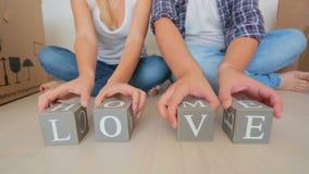Tiro do close up dos pares novos que fazem o amor e a casa das palavras em blocos de madeira filme