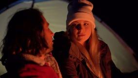 Tiro do close up dos pares novos que sentam-se pelo fogo e que conversam agradavelmente Acampamento com as barracas pelo mar Noit video estoque