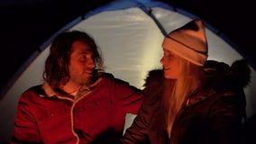Tiro do close up dos pares novos que sentam-se pelo fogo e que conversam agradavelmente Acampamento com as barracas pelo mar Noit vídeos de arquivo