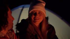 Tiro do close up dos pares novos que sentam-se pelo fogo e que conversam agradavelmente Acampamento com as barracas pelo mar Noit filme