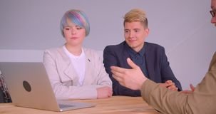 Tiro do close up dos sócios comerciais mulher e homens que têm uma reunião de almoço usando o portátil que senta-se pela tabela n video estoque
