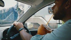 tiro do close-up do Em-carro do homem de negócios relaxado com o relógio esperto que conduz o carro, apreciando o suco de fruta e filme
