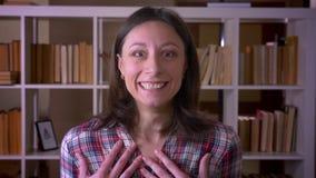 Tiro do close up do estudante fêmea atrativo novo que está sendo excitado e surpreendido olhando a câmera na biblioteca da univer vídeos de arquivo