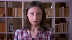 Tiro do close up do estudante fêmea atrativo novo que inclina-se dizendo sim a vista da câmera na biblioteca dentro filme