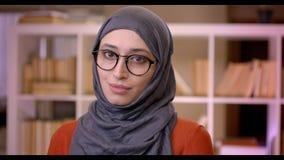Tiro do close up do estudante fêmea bem sucedido muçulmano atrativo novo no hijab e dos vidros que olham a posição da câmera video estoque