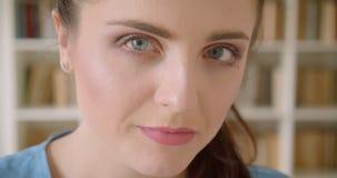 Tiro do close up do estudante fêmea bonito novo que olha alegremente a câmera com as estantes no fundo no filme