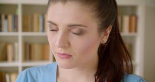 Tiro do close up do estudante fêmea bonito novo que sorri felizmente olhando a câmera com as estantes no fundo no filme