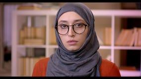 Tiro do close up do estudante fêmea muçulmano atrativo novo no hijab e dos vidros que olham a câmera que está dentro no video estoque