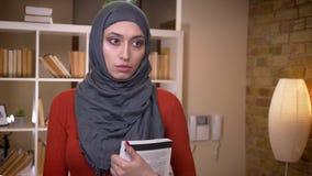 Tiro do close up do estudante fêmea muçulmano atrativo novo no hijab que guarda um livro que está dentro na biblioteca vídeos de arquivo