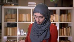 Tiro do close up do estudante fêmea muçulmano atrativo novo no hijab que lê um livro dentro na biblioteca video estoque