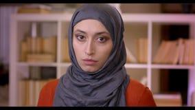Tiro do close up do estudante fêmea muçulmano atrativo novo no hijab que olha a câmera que está dentro na biblioteca vídeos de arquivo