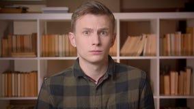 Tiro do close up do estudante masculino caucasiano atrativo novo que inclina-se dizendo sim a vista da câmera na biblioteca de fa filme