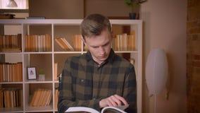 Tiro do close up do estudante masculino caucasiano atrativo novo que lê um livro que olha a câmera na biblioteca de faculdade video estoque