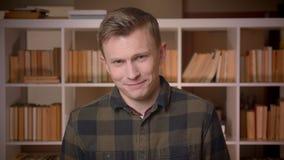 Tiro do close up do estudante masculino caucasiano atrativo novo que sorri com o excitamento que olha a câmera na faculdade video estoque