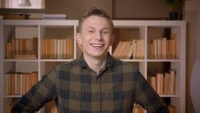 Tiro do close up do estudante masculino caucasiano atrativo novo que sorri e que ri felizmente olhando a câmera na faculdade video estoque