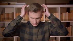Tiro do close up do estudante masculino caucasiano atrativo novo que tem uma dor de cabeça que olha a câmera na biblioteca de fac video estoque
