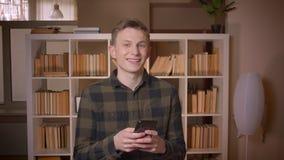 Tiro do close up do estudante masculino caucasiano atrativo novo que usa o telefone que olha a câmera e que sorri na faculdade vídeos de arquivo