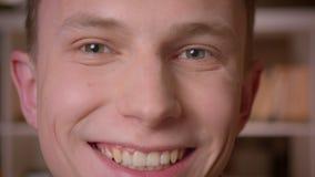 Tiro do close up do estudante masculino caucasiano seguro novo que olha a câmera na biblioteca de faculdade filme