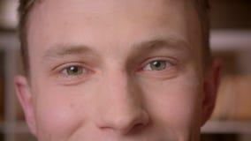 Tiro do close up do estudante masculino caucasiano seguro novo que olha a câmera na biblioteca de faculdade vídeos de arquivo